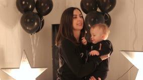 Uma mamã feliz nova está jogando com seu menino de um ano em um estúdio com estrelas