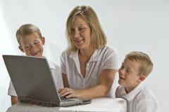 Uma mamã que ensina 6 anos de olds como usar um portátil Foto de Stock