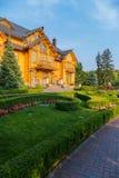 Uma mansão de madeira enorme com um projeto da paisagem sob um céu sem nuvens azul Konka, a residência do museu de Yanukovych de imagem de stock