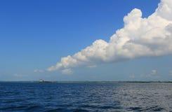 Uma massa das nuvens que apontam para a vila dos ciganos do mar em casa no meio do oceano no fundo do mar raso Fotos de Stock