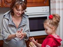 Uma matriz com sua filha está cozinhando foto de stock