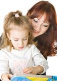 Uma matriz e uma filha que lêem um livro imagens de stock