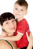 Uma matriz feliz abraça sua criança fotografia de stock
