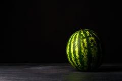 Uma melancia grande inteira em um fundo preto da tabela Verde, duramente e melancia listrada Petiscos frios e doces do verão Imagem de Stock