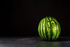 Uma melancia grande inteira em um fundo preto Verde, duramente e melancia listrada Petiscos doces do verão Copie o espaço Fotografia de Stock Royalty Free