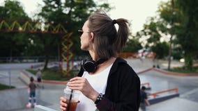 Uma menina à moda nos óculos de sol e nos fones de ouvido aprecia uma bebida em um vidro transparente, bebe através de uma palha  video estoque