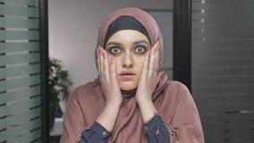 Uma menina árabe nova no hijab vermelho é surpreendida, mostra uma emoção da surpresa Olha a câmera, retrato 60 fps vídeos de arquivo