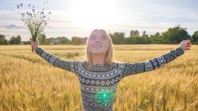 Uma menina adolescente das pessoas de dezesseis anos com as flores das centáureas está girando em um campo fotografia de stock