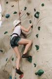 Uma menina adolescente que escala em uma parede da rocha. imagem de stock