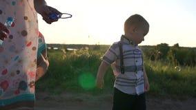 Uma menina adulta faz bolhas e o menino corre-as e morde-, movimento lento filme