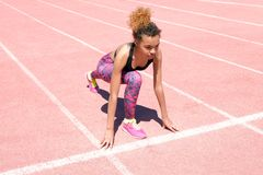 Uma menina afro-americano bonita nova em um t-shirt preto desportivo e em umas sapatilhas cor-de-rosa está preparando-se para com fotografia de stock royalty free