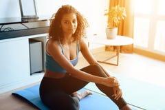 Uma menina afro-americano bonita que faz a ioga exercita em uma esteira da ioga Pratica cedo na manhã em casa fotografia de stock royalty free