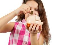 Uma menina agradável deixa cair uma moeda em um mealheiro Fotografia de Stock Royalty Free