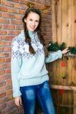 Uma menina agradável está em uma sala com paredes de madeira Ano novo e Chr fotos de stock