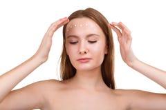 Uma menina agradável, põe um creme sobre sua cara na testa e olha para baixo Isolado imagem de stock royalty free