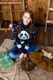 Uma menina agradável senta-se em uma sala com paredes de madeira Ano novo e Chris Fotografia de Stock