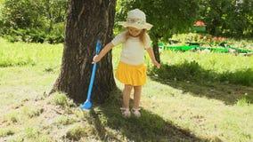 Uma menina ajunta a grama segada no verão video estoque
