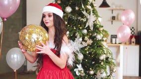 Uma menina alegre e bonita com cabelo escuro está vestindo um terno vermelho de Santa Claus e está levantando-o para a câmera, in filme