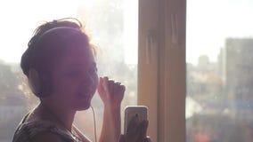 Uma menina alegre em danças do nuashniki, escuta a música do telefone Olha a câmera, sorrindo, contra video estoque