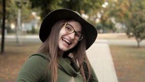 Uma menina alegre em um parque no outono, chamando um amigo Emoção, uma menina em um chapéu e vidros filme