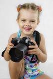 Uma menina alegre mantem a câmera de SLR Fotografia de Stock Royalty Free