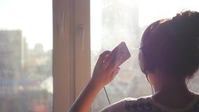 Uma menina alegre nova está perto de uma janela com um telefone em seus mãos e fones de ouvido, conflitos música, danças, nos rai video estoque