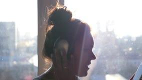 Uma menina alegre nova nos fones de ouvido e com um telefone em suas mãos dança e canta a posição perto da janela no vídeos de arquivo