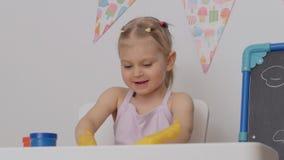 Uma menina alegre pequena que senta-se na tabela no desenho da sala de crian?as com pinturas do dedo no papel, manchou suas m?os video estoque