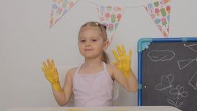 Uma menina alegre pequena que senta-se na tabela no desenho da sala de crian?as com pinturas do dedo no papel, manchou suas m?os filme
