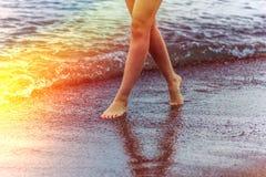 Uma menina anda ao longo do litoral no tempo do por do sol foto de stock