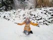 Uma menina anda em um parque coberto de neve imagem de stock royalty free