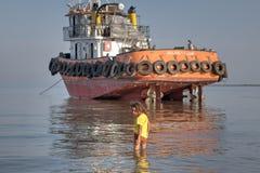 Uma menina anda joelho-profundo no seawater, Irã do sul Fotografia de Stock
