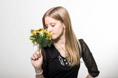 Uma menina aprecia flores Imagem de Stock Royalty Free
