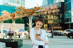 Uma menina aprecia o Internet com um telefone celular no fundo de uma construção do centro de negócios imagens de stock