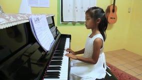 Uma menina asiática bonito no vestido branco joga o piano video estoque