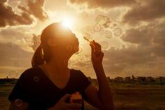 Uma menina asiática do sudeste está fundindo bolhas no ar no sunse Foto de Stock