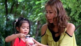 Uma menina asiática está comendo o queque delicioso com mãe vídeos de arquivo