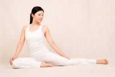 Uma menina asiática que faz a ioga fotografia de stock