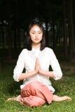 Uma menina asiática que faz a ioga imagem de stock