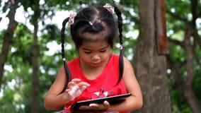 Uma menina asiática que joga o jogo na tabuleta filme