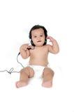 Uma menina asiática nova escuta a música com auscultadores Fotografia de Stock