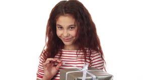 Uma menina astuto desembala seu presente do ano novo imagem de stock