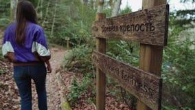 Uma menina atlética anda ao longo de um trajeto após um letreiro de madeira na floresta vídeos de arquivo