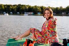 Uma menina atlética nova na veste senta-se no cais Foto de Stock Royalty Free