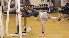 Uma menina atlética nova que faz um exercício em um cruzamento no gym filme