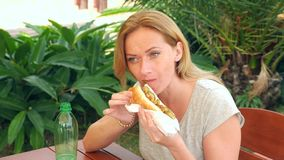 Uma menina atrativa come o pão fresco do pão árabe com uma salada de legumes frescos e de carne, sentando-se em um café do fast f video estoque