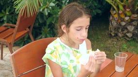 Uma menina atrativa come o pão fresco do pão árabe com uma salada de legumes frescos e de carne, sentando-se em um café do fast f filme