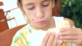 Uma menina atrativa come o pão fresco do pão árabe com uma salada de legumes frescos e de carne, sentando-se em um café do fast f vídeos de arquivo