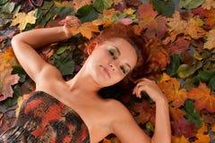 Uma menina atrativa do redhead está encontrando-se nas folhas fotografia de stock