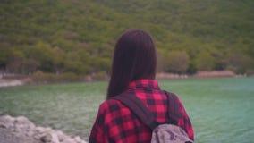 Uma menina atrativa em uma camisa de manta vermelha, levantando para a câmera A menina vai ao longo da costa do lago em um dia mo filme